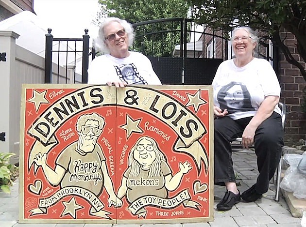 Dennis and Lois with their gate sign, made by The Mekons' Jon Langford